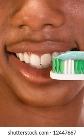 Close up of Afro-American female brushing her teeth