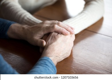 Close up of aged couple hold hands showing eternal support and love, senior husband embrace wife express care and empathy, elder man caress comforting beloved woman. Relationships goal, family concept