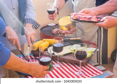 close up with a lot of aged hands prepared meal with barbeque outdoor. fresh food like meal and vegetable and mais pop corn cooked on the flame. group of people in nice activity for elderly