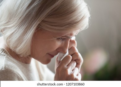 Close up of aged woman feel upset crying remembering good old times, sad senior female wipe tears from face disappointed by life problems, lonely elderly lady in despair having difficulties