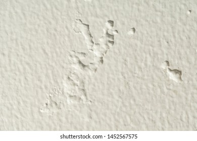 Close up air bubbles in paint on a concrete wall cause by moisture, damp surface.
