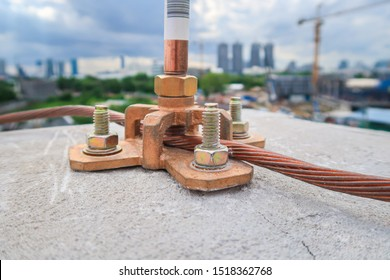 Close up Air terminal rod and bare copper cable install on rooftop of high building for Lightning protection and protect electrical equipment damage when raining and lightning strike. Selective focus.