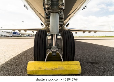 Close up aircraft nose landing gear on the tarmac with chock at the tire