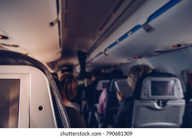 Close up of airplane aisle seat in fully occupied airplane interior