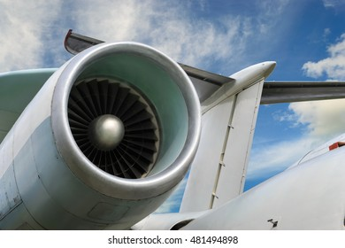 Close up of airplane jet engine, parts of the aircraft fuselage and tail on cloudy sky background