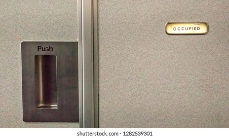 Close up of an airplane lavatory door, with occupied sign on.