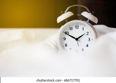 Close up .Alarm clock on white mattress.copy space.