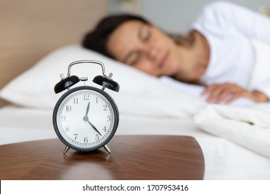 Close up alarm clock on wooden bedside table showing late night, peaceful woman sleeping on background under warm blanket in comfortable bed, young female resting in bedroom, enjoying dreams