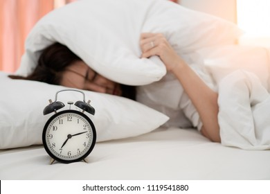 Close up alarm clock with young asian woman lazy waking up in early morning for routine daily job. Sleepy girl lying on bed closing her eyes and try to hiding under pillow for  snooze alarm clock.