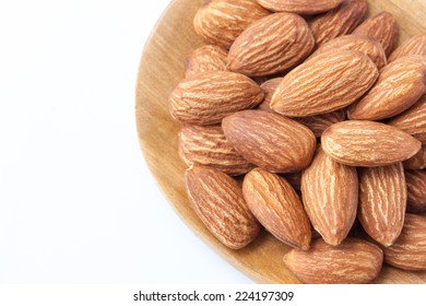 Close up of almonds on a wooden spoon isolated on white