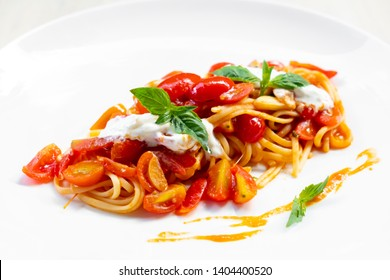 close up of an amazing fine dining italian pasta spaghetti pomodoro, cherry tomato, sauce, burrata cheese, basil, garlic, olive oil, in a white plate ,natural back light, professional skilled chef