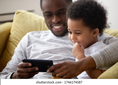 Close up American caring dad spend time with little son family sitting on sofa using smartphone watching cartoons having fun enjoy on-line app for kids. Parental control lazy weekends activity concept