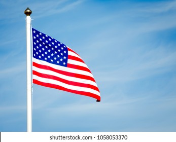 Close up of American flag blowing in the wind. The 50 stars on the flag represent the 50 states of the United States of America, and the 13 stripes represent the thirteen British colonies.