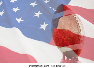 Close up of American football on tee against american flag with stars and stripes