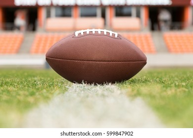 Close up of American football on the yard line of a stadium field.