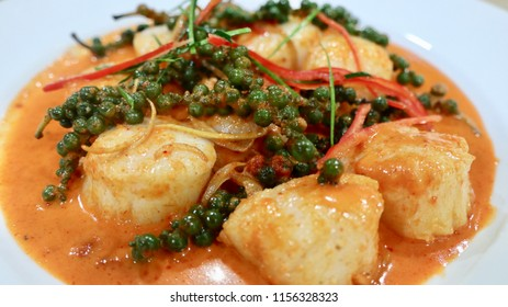 Close up of American scallops big size are cooked with curry paste decorated with young fresh peppers, slices of red and green chilis to promote colorful delicious dish. Perfect for wonderful meal