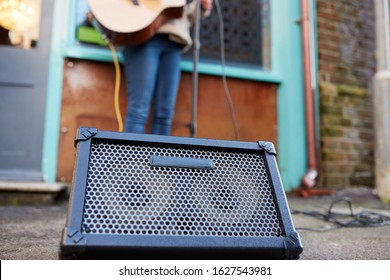 Close Up Of Amplifier As Female Musician Busks Playing Acoustic Guitar Outdoors In Street