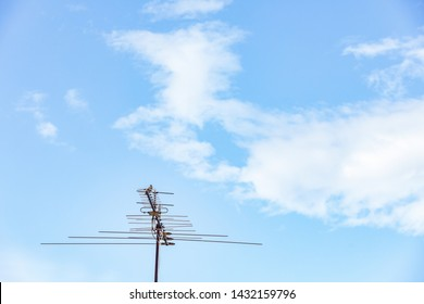 Close up analog television signal tower with clear sky in background.