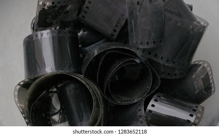 Close up of ancient 35mm black and white negative film rolls, worn, dusty and badly kept analogue photographic film.