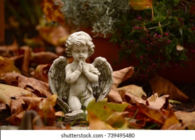 Close up of a angel child statue by a grave
