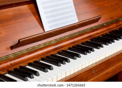 a close up angle view of a rosewood piano keyboard with blank sheet music staff paper