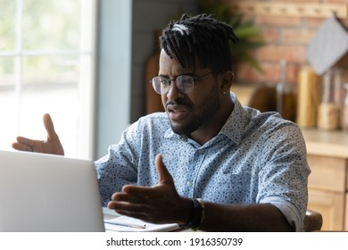Close up angry annoyed African American man wearing glasses having problem with broken laptop, computer crash, data loss, looking at screen, unhappy confused businessman reading unexpected bad news