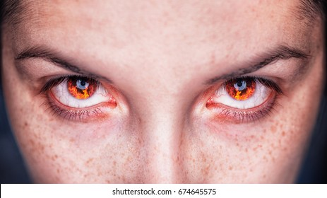 Close up of angry look of woman - young girl eyes with burning fire in the eyes