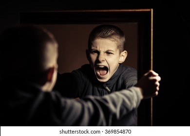Close up Angry Young Boy Shouting on his Own Mirror Reflection with Mouth Wide Open Against Black Background.