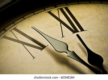 Close up of an antique clock and the time is almost midnight. Concept of time,the past or deadline.