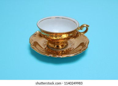 Close up of an antique, golden tea cup, isolated on white background.