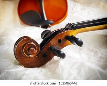 Close up antique Scroll violin,part of acoustic instrument,blurry light around,vintage and art tone