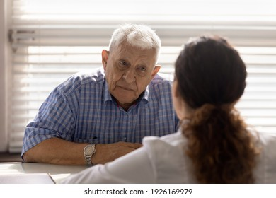 Close up anxious serious old man listening to female doctor at meeting in hospital, therapist physician consulting mature patient about disease, treatment, elderly generation healthcare concept