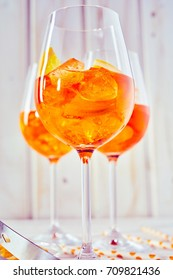 A close up of aperol orange spritz cocktails, glasses and mixing equipment on a plain white timber background in vertical portrait orientation.
