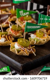 A close up of appetizers made of nacho scoops filled with guacamole, sour cream, cheese and salsa and topped with a jalapeno on a dark wooden platter.