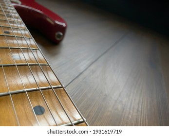 close up apple red scallop electric guitar neck and nickel stings on veneer wood background with copy space for letter. business and music concept. Wallpaper or background for book.
