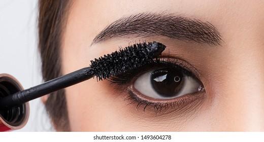 Close up applying mascara brush on eyelash. Applying cosmetic make up  eyelash Extensions. Asian eye make up cosmetics.