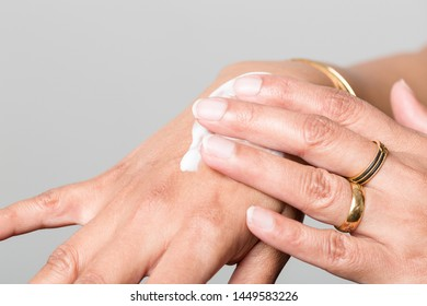 Close up of applying skin cream on female hand