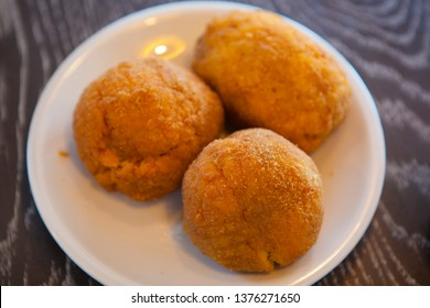 Close up Arancino is a stuffed rice ball that is coated with bread crumbs and then deep fried. Local Traditional Sicilian food. Arancini. South Italy. Italian dishes. Fast food. Mediterranean cuisine.