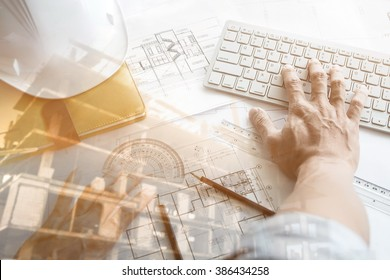 Close up of Architect working on blueprint with computer at workplace.Double exposure of construction site.