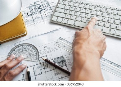 Close up of Architect working on blueprint with computer at workplace.