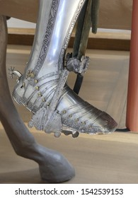 Close up of armored boot with spur on saddle  stirrup . Medieval equipment of armored knight.