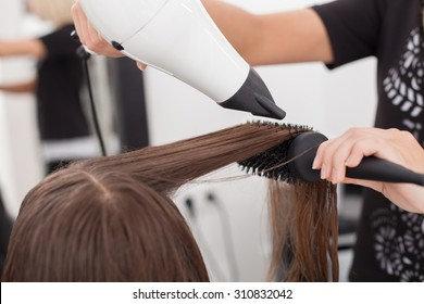 Close up of arms of hairstylist drying female hair with a fen. The woman is holding a hairbrush