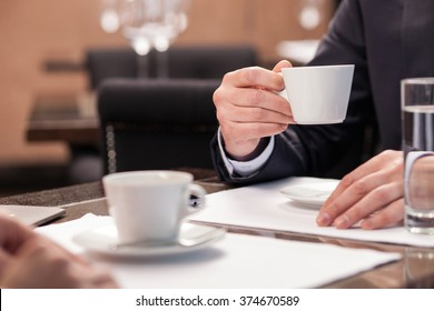 Close up of arms of successful business having a business meeting with his client in cafe. The man in suit is drinking coffee