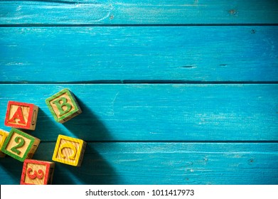 Close up arrangement of alphabet on blue background. Copy-space, preschool, education concept or other your content. Long shadow and vignette effect.