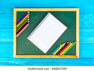 Close up arrangement of pencil color, book and chalk board on blue background. Preschool, education, back to school and copy-space concept or other your content.