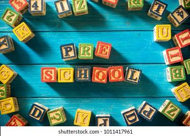 "Close up arrangement of ""Preschool"" alphabet on blue background. Preschool, education concept or other your content. Long shadow and vignette effect."