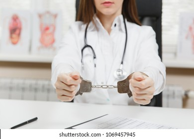 Close up arrested female doctor sitting at desk with medical documents in light office in hospital. Woman in medical gown, stethoscope, hands with handcuffs in consulting room. Medicine, law concept