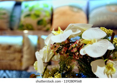 Close up of artificial flowers in a homeware store, with cushions in out of focus background