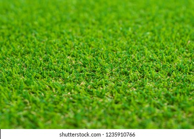 Close up to artificial turf piles. Macro with selective focus of artificial grass.
