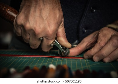 Close up of an artisan working with leather in his laboratory